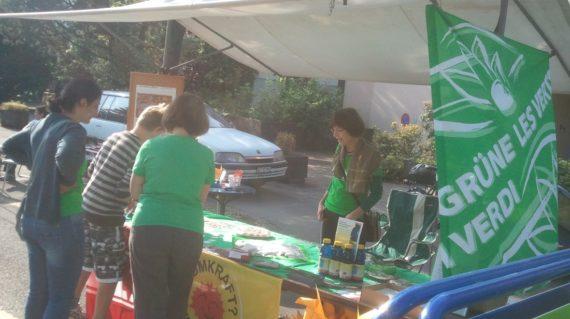 """Mehrere Personen stehen um den Grünen Stand am Herbstmärit, welcher mit Grünen und """"Atomstrom Nein Danke""""-Fahnen geschmückt ist."""